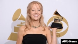 "FILE - Maria Schneider poses in the press room with the award for best contemporary classical composition for ""Schneider, Maria: Winter Morning Walks"" at the 56th annual Grammy Awards at Staples Center, Jan. 26, 2014, in Los Angeles."