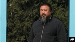 Chinese avant-garde artist Ai Weiwei stands at the doorway to his home where he is under house arrest in Beijing Saturday, Nov. 6, 2010.