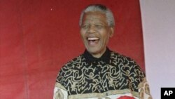 L'ancien président sud-africain Nelson Mandela fête la veille de son 77e anniversaire avec des enfants à Johannesburg, le 17 juillet 1995, où il a obtenu son premier emploi en tant que policier.