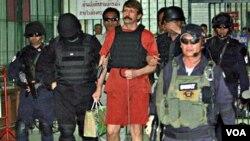Tersangka penjual senjata Rusia, Victor Bout, meninggalkan pengadilan di Bangkok.