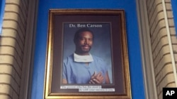 FILE - In this May 3, 2018 photo, a portrait of Ben Carson hangs in the Ben Carson Reading Room inside of the Archbishop Borders School in Baltimore.