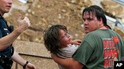 Seorang warga mengangkut seorang anak dari gedung sekolah di Plaza Towers setelah tornado menyerang kota Moore, Oklahoma (20/5).