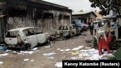 Des Congolais passent devant une maison et des véhicules qui ont brûlé lors des manifestations anti-gouvernement à Kinshasa, RDC, le 21 septembre 2016.