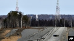 A Russian Soyuz rocket, center in the background, carrying satellites stands on the launch pad at the new Vostochny Cosmodrome near Uglegorsk, the city in eastern Siberia in the Amur region, Russia, April 27, 2016.