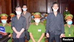 អ្នកកាសែតរបស់សមាគមអ្នកកាសែតឯករាជ្យវៀតណាម លោក Pham Chi Dung (ស្ដាំ) លោក Le Huu Minh Tuan (កណ្ដាល) និងលោក Nguyen Tuong Thuy (ឆ្វេង) ឈរនៅចន្លោះប៉ូលិស ក្នុងអំឡុងពេលនៃសវនាការរបស់ពួកគេនៅទីក្រុងហូជីមិញ ប្រទេសវៀតណាម ថ្ងៃទី៥ ខែមករា ឆ្នាំ២០២១។