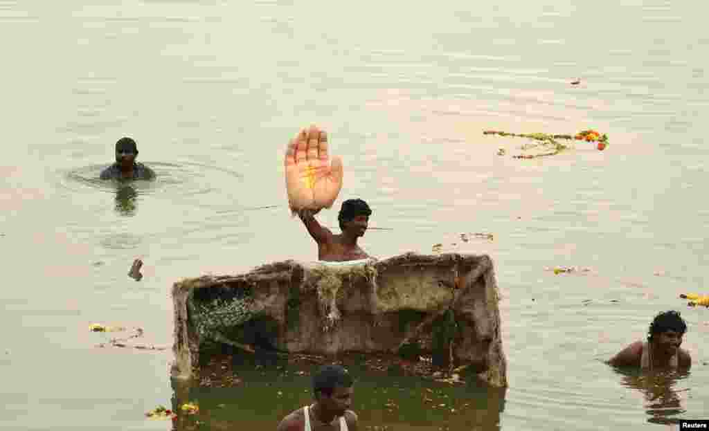 A man holds the hand of an idol of the Hindu elephant god Ganesh, the deity of prosperity, during idol immersion ceremony in the Hussain Sagar lake during the Ganesh Chaturthi festival in the southern Indian city of Hyderabad.