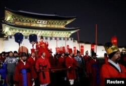 13일 서울 광화문 앞에서 열린 평창동계올림픽 성화봉송행사에서 임금 복장의 성화주자가 어가행렬로 성화를 봉송하고 있다.