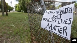 A sign calling for justice is attached to a fence near the site where Walter Scott was killed in North Charleston, S.C., Wednesday, April 8, 2015.