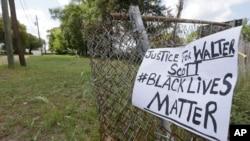 在斯科特被枪杀地点附近的栅栏上挂着一个呼吁执法公正的标语牌(2015年4月8日)