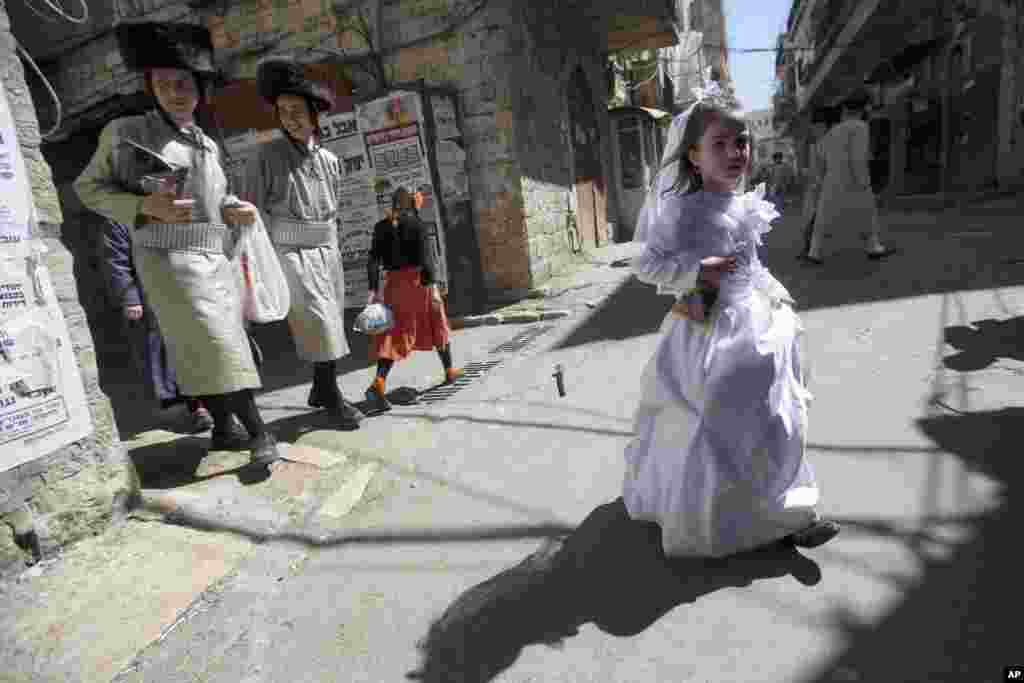 Ultra-Orthodox Jewish youths walk next to a girl in costume during Purim celebrations in Jerusalem. The festival commemorates the rescue of Jews from genocide in ancient Persia recorded in the biblical Book of Esther.