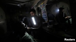FILE - A barber holds a portable emergency light in his mouth while shaving a customer during a power outage at a low income neighborhood in Karachi, Pakistan, June 29, 2013. Pakistan faces a year-round electricity shortfall that hits around 7,000 megawatts in the summer.