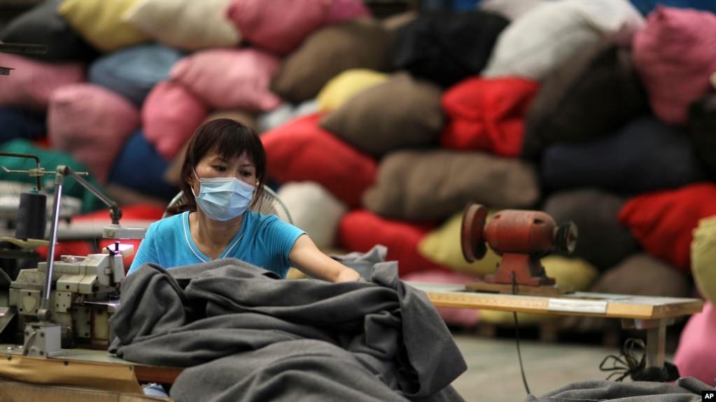 一名台湾志愿者在台北的慈济基金会工厂用再生塑料制作毯子。(资料照片)