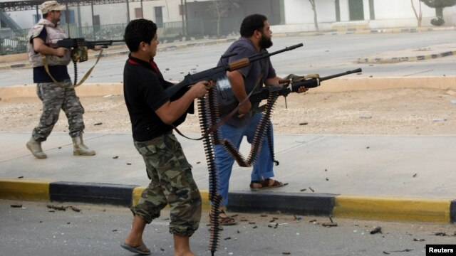 Militia fighters are seen shooting at a building in the center of Bani Walid, Libya, October 24, 2012.