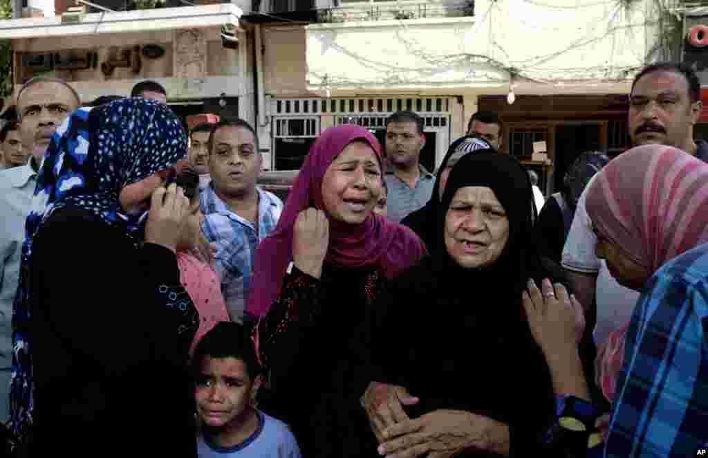 Egyptian women weep near the scene after a roadside bomb went off on a busy street in downtown near the foreign ministry in Cairo.