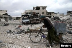 FILE - A man walks with his bicycle through a debris-littered site in the besieged town of Douma, eastern Ghouta, near Damascus, Syria, March 30, 2018.