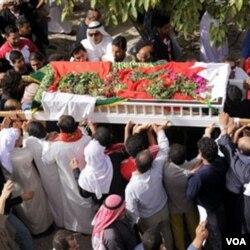 Warga Bahrain memakamkan seorang korban tewas akibat bentrokan dalam protes di Lapangan Mutiara, Manama Jumat (18/2).