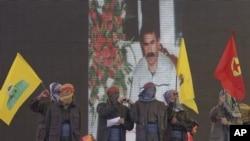 Des supporters masqués agitent des drapeaux du PKK devant un écran montrant le chef rebelle kurde emprisonné Abdullah Ocalan, Diyarbakir, Turquie, jeudi 21 mars, 2013.