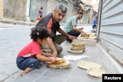 FILE - Residents spread bread for cooling in Old Aleppo, Syria.