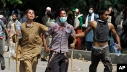 Pakistani protesters help escort their injured colleague to an ambulance during a protest near prime minister's home in Islamabad, Sunday, Aug. 31, 2014.