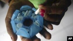 Seorang perempuan dengan HIV menyiapkan obat-obatannya.