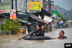 Seorang perempuan menggunakan rakit dari ban mengarungi banjir setelah hujan deras menyebabkan banjir di Bekasi, Jawa Barat, 1 Januari 2020. (Foto: AFP)