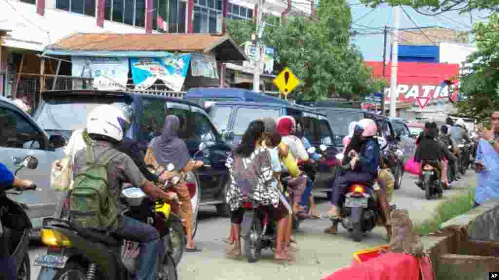 People on motorcycles in Aceh rushing to higher ground. (VOA Photo - Budi Nahaba)