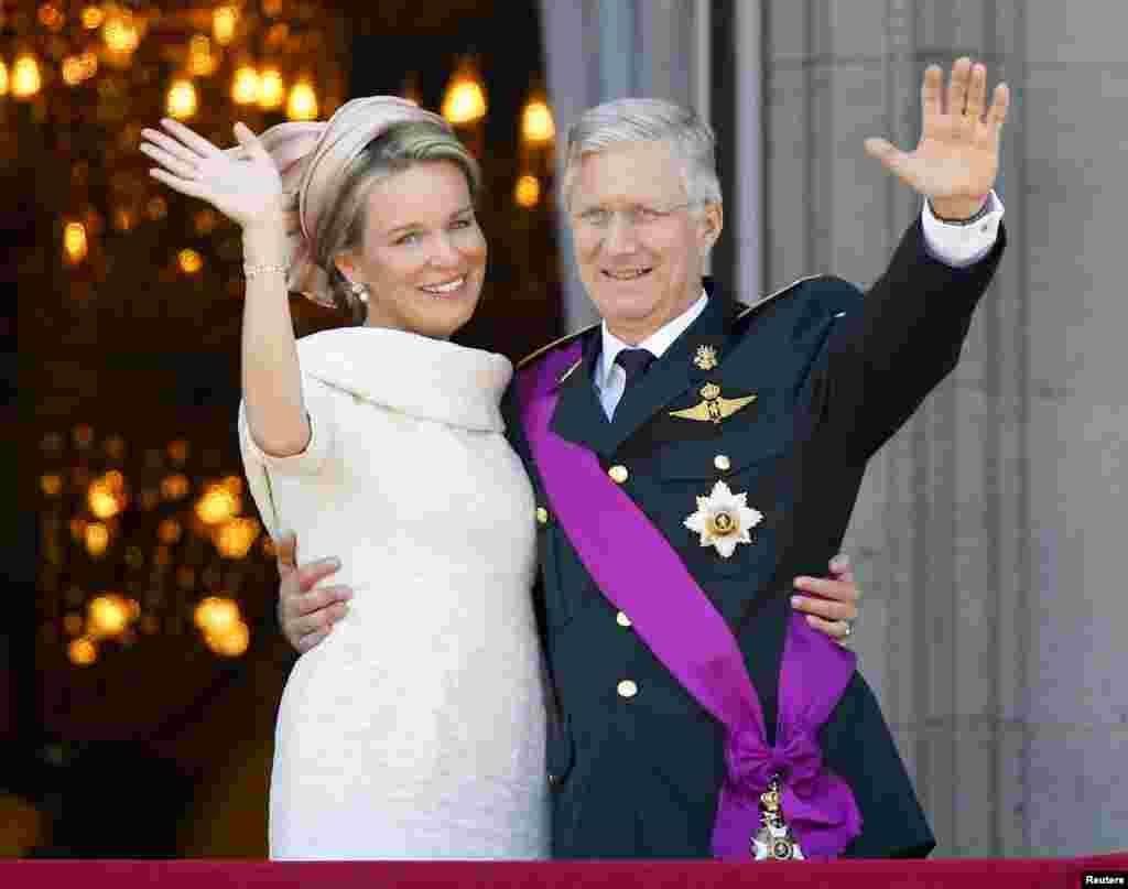 Los reyes de Belgica Mathilde y Aberto saludan desde el balcón del Palacio Real en Bruselas durante las celebraciones del día nacional y la investidura de Felipe.