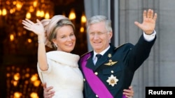 ເຈົ້າຊີວິດອົງໃໝ່ຂອງເບລຢ້ຽມ: ກະສັດ Philippe ກັບພະລາຊິນີ Mathilde ຊົງໂບກພະຫັດໃຫ້ປະຊາຊົນ ຈາກລະບຽງຂອງພະລາດຊະວັງ ຢູ່ນະຄອນຫຼວງ Brussels, ວັນທີ 21 ກໍລະກົດ 2013. ເບລຢ້ຽມສະເຫຼີມສະຫຼອງວັນຊາດ ໃນມື້ນີ້ ຊຶ່ງເປັນມື້ດຽວກັບທີ່ ກະສັດ Albert II ຊົງສະຫຼະບັນລັງ ໃຫ້ພະໂອລົດ.
