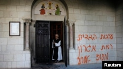 A monk stands next to graffiti sprayed on a wall at the entrance to the Latrun Monastery near Jerusalem, Sep. 4, 2012.
