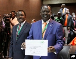 Orange Democratic Party presidential candidate, Raila Odinga (R), displays his registration certificate, with running mate Vice President Kalonzo Musyoka (L), in Nairobi, Kenya, Jan. 30. 2013.