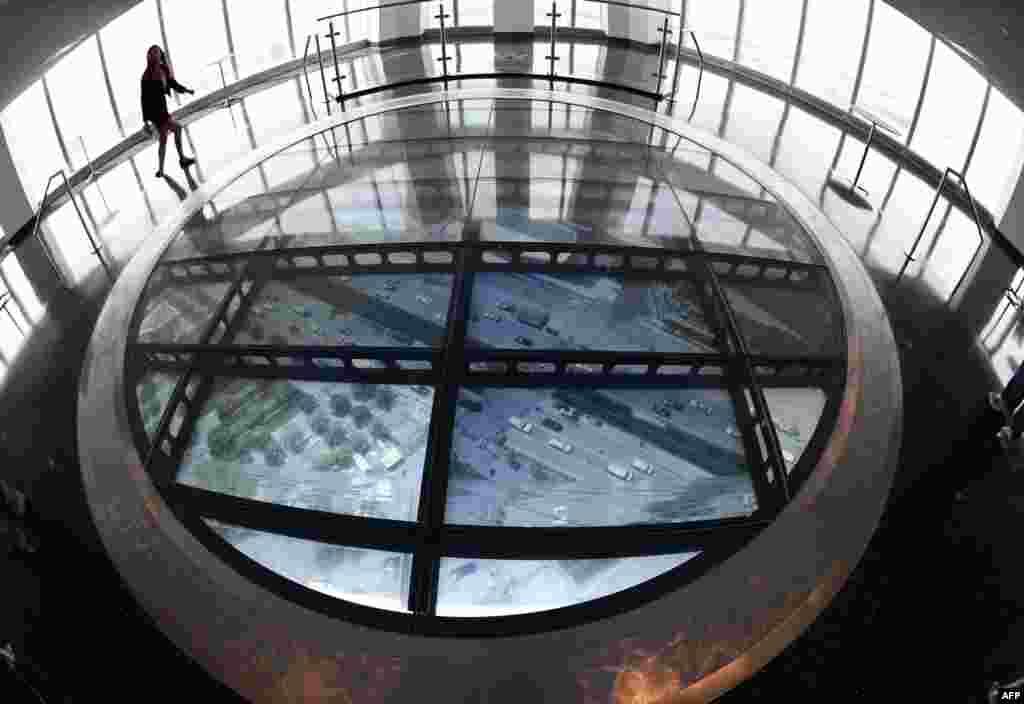 សមាជិកនៃក្រុមប្រព័ន្ធផ្សព្វផ្សាយម្នាក់ ឈរនៅលើកញ្ចក់មានរាងមូលដូចឌីសមានទទឹងទំហំជាង៤ម៉ែត្រហៅថា «Sky Portal» ដែលអាចឲ្យមើលឃើញទិដ្ឋភាពផ្លូវពីក្រោមអគារយ៉ាងច្បាស់ នៅក្នុងមជ្ឈមណ្ឌល One World Observatory ក្នុងទីក្រុងញូវយ៉ក។