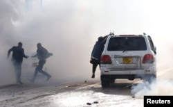 Politicians run after riot police fired tear gas to disperse the convoy of Kenyan opposition leader Raila Odinga of the National Super Alliance (NASA) coalition upon Odinga's return to Nairobi, Nov. 17, 2017.