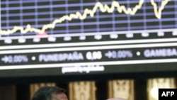 Traders look at a stock index board at Madrid's bourse, January 16, 2012