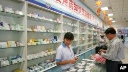 中國北京,一名工作人員在藥店為顧客服務(2004年9月29日)。
