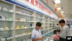 中国北京,一名工作人员在药店为顾客服务(2004年9月29日)。