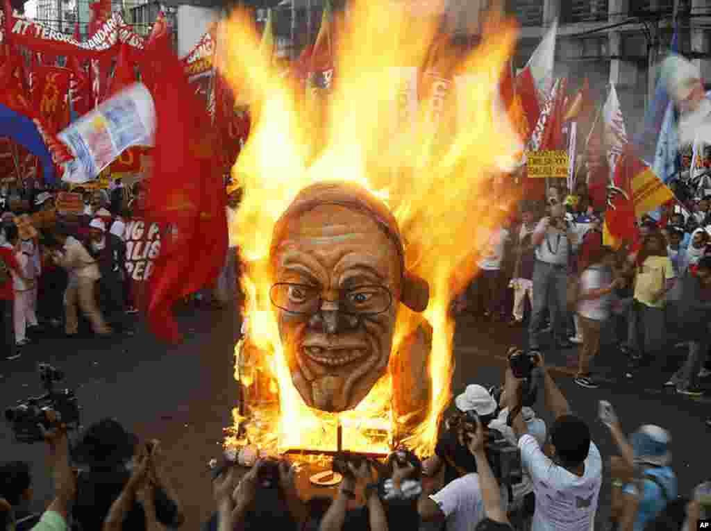 ພວກປະທ້ວງທີ່ຟີລິບປີນ ຈູດຮູບຫຸ່ນຂອງປະທານາທິບໍດີBenigno Aquino III ໃນລະຫວ່າງການໂຮມຊຸມນຸມ ຢູ່ໃກ້ໆທໍານຽບ ປະທານາທິບໍດີ ທີ່ນະຄອນຫລວງມະນີລາ ເພື່ອສະຫລອງວັນກໍາມະກອນ ສາກົນ, ວັນທີ 1 ພຶດສະພາ ຫລື May Day ທີ່ຟີລິບປີນ. (AP Photo)