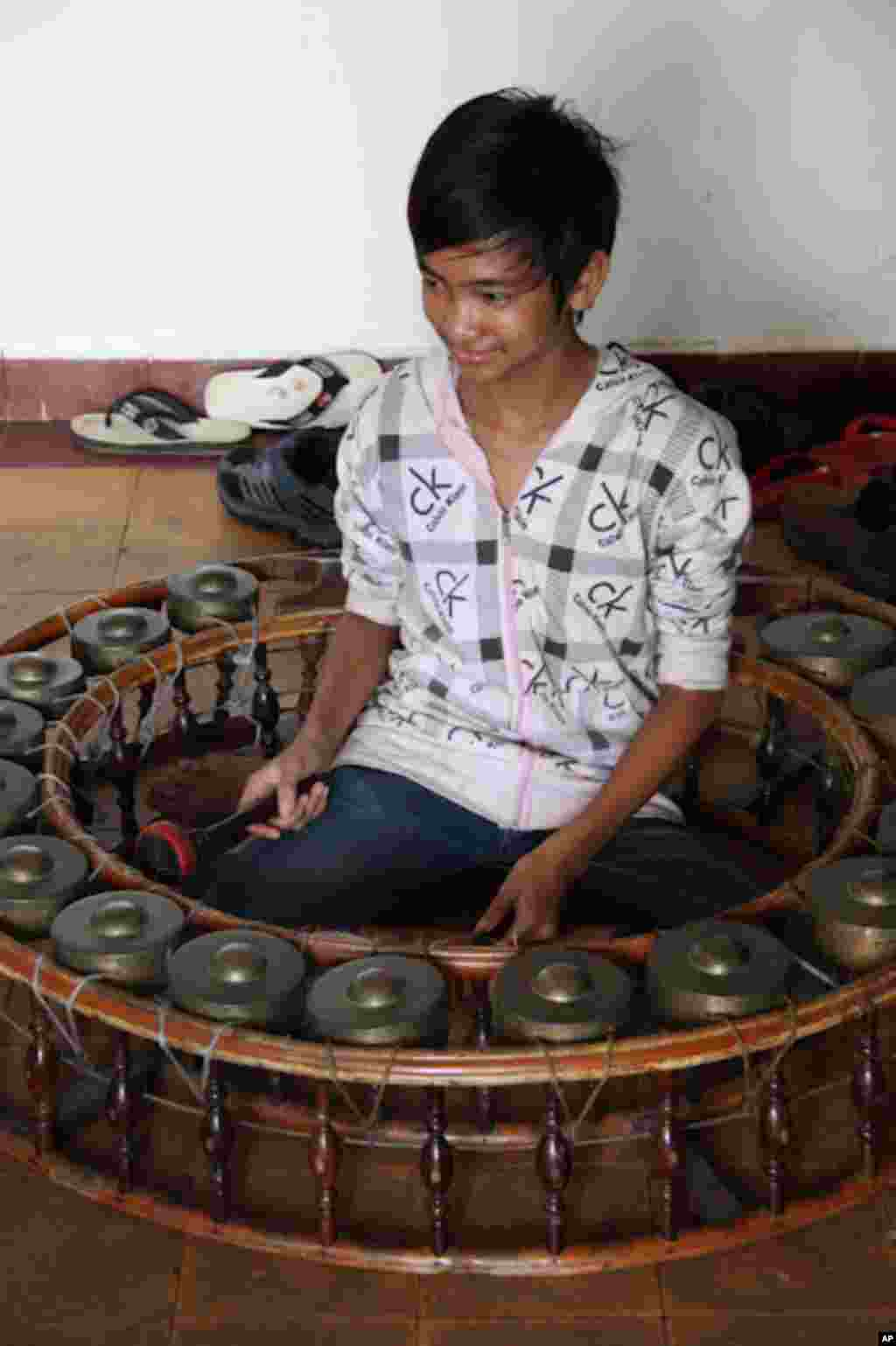 Cambodian Living Arts student Lay Roza learns to play the small kong in Phnom Penh, February 28, 2012, (VOA - D. Schearf).