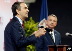 FILE - Democratic candidate for Virginia governor Ralph Northam, left, gestures during a debate with Republican challenger Ed Gillespie, at the University of Virginia-Wise, in Wise, Virginia, Oct. 9, 2017. Defeated by Northam, Gillespie was being closely watched by Republican strategists gauging how him distancing himself from President Donald Trump would fair with voters.