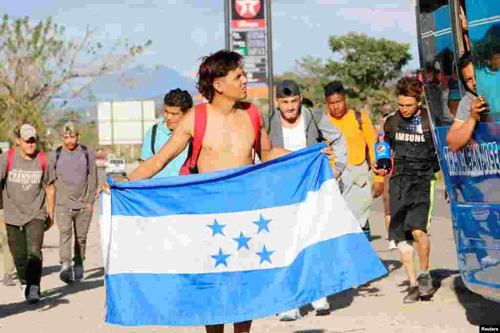 Uno de los integrantes de la caravana de migrantes sostiene una bandera nacional hondureña, en su camino hacia Estados Unidos, en Cucuyagua.