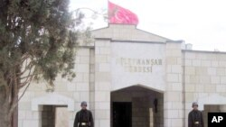 FILE - Turkish soldiers stand guard at the entrance to the memorial site of Suleyman Shah, grandfather of Osman I, founder of the Ottoman Empire, in Karakozak village, northeast of Aleppo, Syria, April 2011.