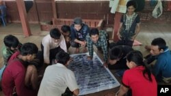 In this March 2020 photo provided by the Southern Youth Development Organization, community members check information in a poster they produced which documents local fish, before publication, in the Lenya area of the Tanintharyi region in southern Myanmar.