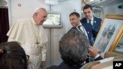 Papa Franoa prima poklon od novinara tokom leta iz Abu Dabija ka Rimu, 5. februara 2019.