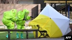 2018年3月8日,身穿防護服的英國工作人員在英國南部索爾茲伯里的斯科利帕中毒現場勘查。