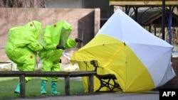 Des membres des services d'urgence installent une tente sur le banc où l'espion russe Sergei Skripal et sa fille Yulia ont été retrouvés dans un état critique à Salisbury, Angleterre, le 8 mars 2018.