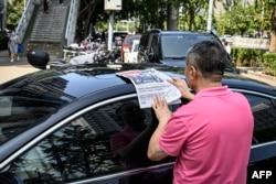 一名男子在北京街頭閱讀中共官媒環球時報對塔利班佔領喀布爾的報導。 (2021年8月17日)