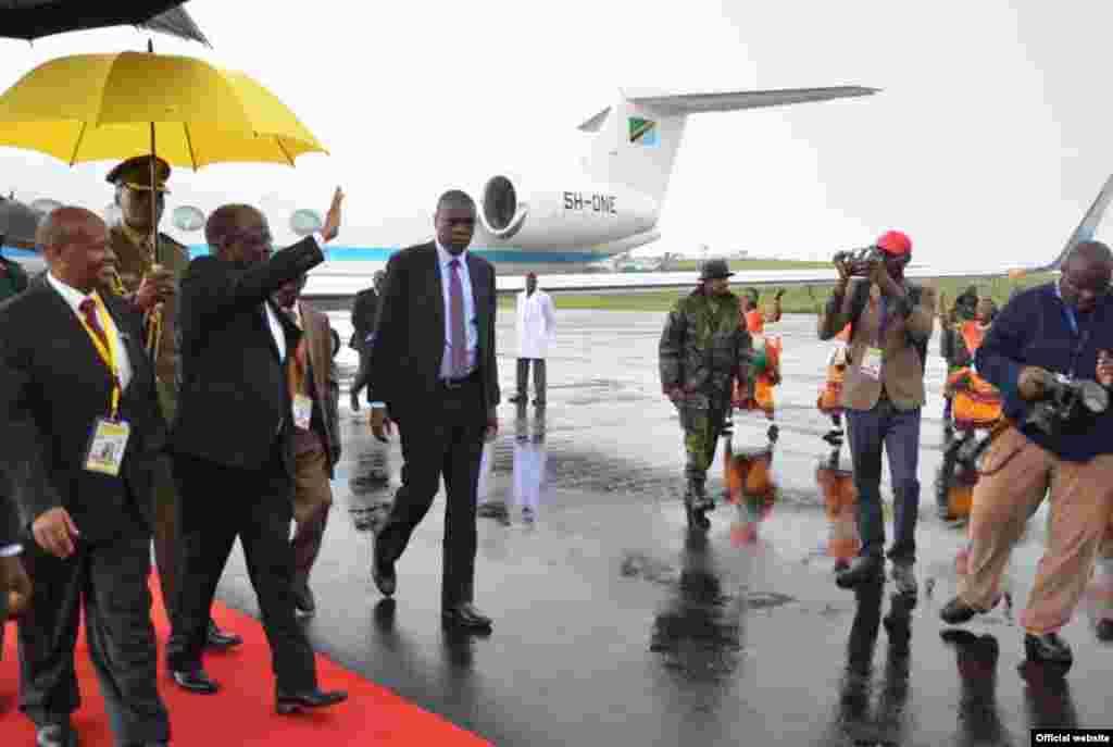Rais wa Jamhuri ya Muungano wa Tanzania Dkt. John Pombe Magufuli akipunga mkono kwenye kikundi cha ngoma mara baada ya kuwasili kwenye uwanja wa Entebe nchini Uganda.
