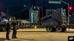 Cảnh sát đứng cạnh một chiếc xe bọc thép sau khi tìm kiếm gần một khu vực ở San Bernardino sau vụ nổ súng, ngày 2/12/2015.