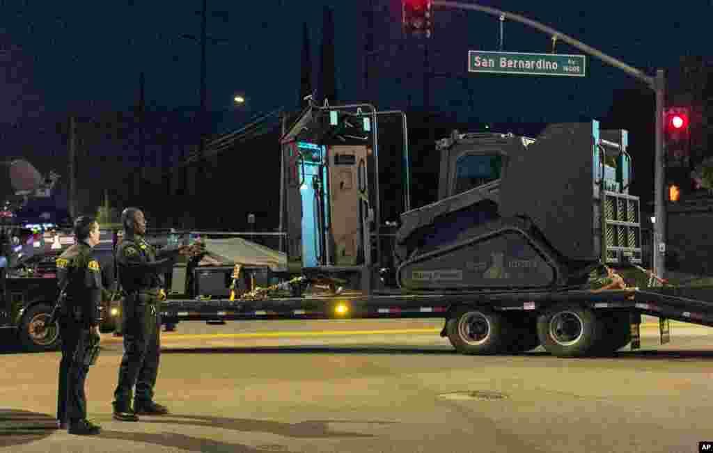 Les autorités de Californie se tiennent près d'un véhicule blindé près du lieu où la police a arrêté un véhicule suspect à San Bernardino, en Californie, 2 décembre, 2015.