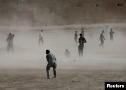Ko'chada futbol o'ynayotgan afg'on yoshlar