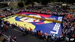 """Partidarios del líder opositor encarcelado Leopoldo López exhiben un mosaico gigante con una imagen de él que lee en español """"Libertad ahora"""" durante un mitin en Caracas, Venezuela, el sábado 18 de febrero de 2017."""